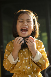 funny face of asian children holding headphone in hand