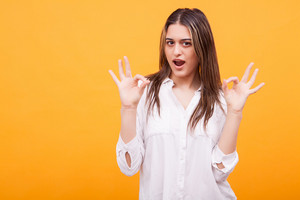 Funny young girl in white shirt showing ok sign over yellow background. Hand gesture