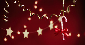 Garlands and golden ribbon on red background with hanging candy cane
