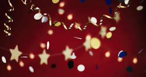 Garlands and golden ribbon on red background with multicolor confetti