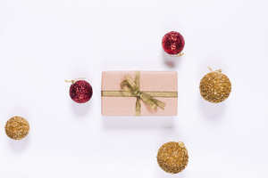 Gift box with gold bow and Christmas balls on a white background top view