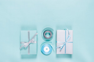 Gift boxes and ribbons and on a blue background top view