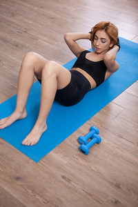 Girl doing abs crunches during her home training. No pain no gains.