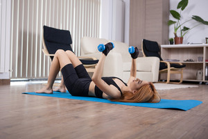 Girl doing home chest workout with dumbbels. Girl getting in shape,