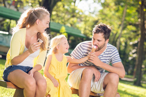 Girl feeding her father with an ice-cream in the park