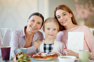 Girl, her mother and grandmother sitting by table and looking at camera