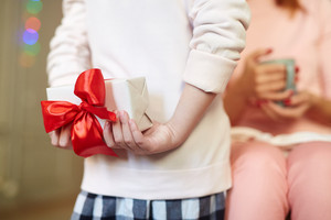 Girl hiding package with red ribbon behind her back
