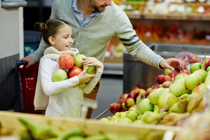 Girl holding heap of green and red apples while her father choosing them
