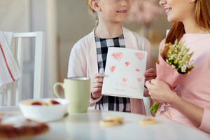 Girl holding self-made greeting-card for her mother
