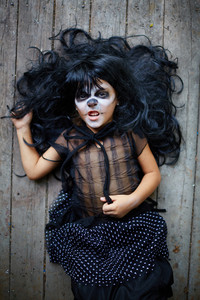 Girl in black wig and halloween attire lying on wooden floor