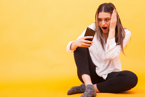 Girl looking amazed at her phone while sitting down over yellow background. Facial expression