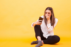 Girl looking shocked at her phone while sitting down over yellow background. Facial expression