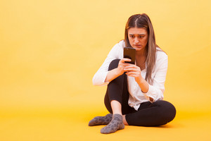 Girl looking worried at her phone while sitting down over yellow background. Facial expression