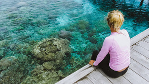 Girl sitting on a wooden jetty near Mansuar island in Raja Ampat. Beautiful colorful corals visible in transparent crystal clear water. West Papua, Indonesia