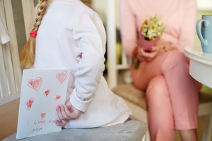 Girl sitting on chair with handmade greeting-card for mother behind her back
