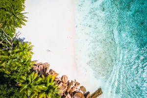 Girl sunbathing on tropical sandy beach surrounded by brown rocks, coconut palm trees and turquoise azure ocean lagoon. Aerial drone shot. Seychelles