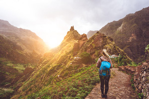 Girl walking down along the trekking route to verdant Xo-Xo valley. Warm sunlight seable on horizont. Santo Antao Island Cape Verde