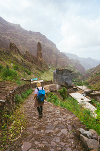 Girl with backpack walking down along the trekking route to verdant Xo-Xo valley. Mountain peaks and local village is visible in front. Santo Antao Island Cape Verde