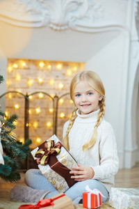 Girl with present sitting on the floor by fireplace
