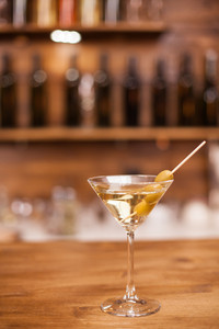 Glass of dry martini with green olives on a rustic wooden bar counter. Refreshment drink. Nightlife. Closeup