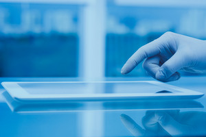 Gloved hang of scientist or medical worker using digital tablet