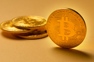 Gold bitcoin cryptocurrency coins on yellow backgound