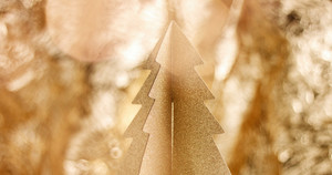 Golden cardboard Cristmas tree close up with sparkling stars and lens flare in warm gold tones. loop
