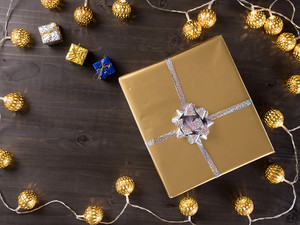 Golden christmas gift box with golden christmas lights on wooden background. Small presents.