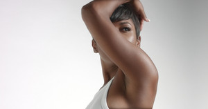 Gorgeous black young woman dancing and posing video. white body suit, ideal skin,