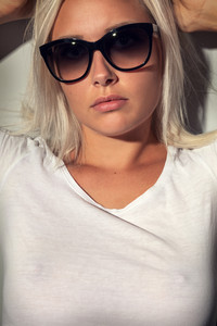 Gorgeous blonde woman with sunglasses in warm colored light