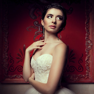 Gorgeous bride in wedding dress in vintage interior. Studio lights shooting. Retro red walls. Happy young bride. Wedding day