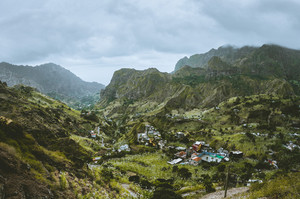 Gorgeous panorama view of a fertile Paul valley. Agriculture terraces of sugarcane in vertical valley sides, dwellings, rugged peaks and motion clouds on horizon