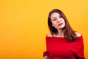 Gorgeous young woman in her 20s looking at the camera over yellow background. Pretty girl. Attractive caucasian.