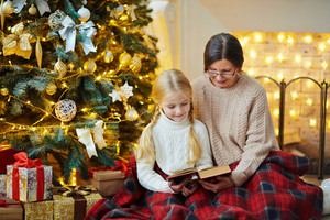Grandmother and granddaughter reading xmas story at home