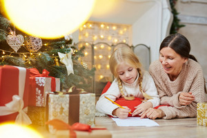 Grandmother teaching her granddaughter how to make xmas greeting card