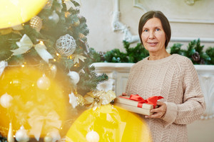 Grandmother with gift-box looking at camera on xmas eve