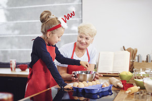 Grandmother with girl baking in the kitchen