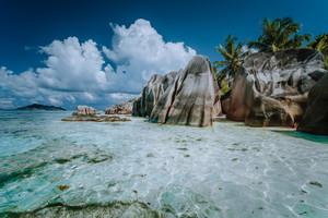 Granite boulders in shallow ocean water and white cloudscape on amazing Anse Source D'Argent tropical beach, La Digue Seychelles. Luxury exotic travel concept