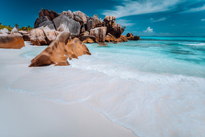 Granite rocks boulders, perfect white sand, turquoise water, blue sky. paradise beach Anse Cocos on the Seychelles. Vacation background