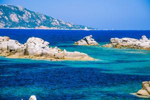 Granite rocks in sea, amazing azure water, white sailboat in background near Porto Pollo, Sardinia, Italy