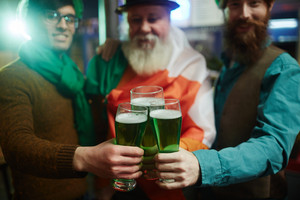 Green beer held by three friends in pub