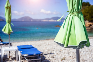 Green sunbed umbrella on white stoe beach by clear turquoise blue waters of Mediterranean sea on sunny hot summer day