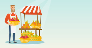 greengrocer standing near the stall with fruits and vegetables. Greengrocer standing near the market stall. Greengrocer holding basket with fruits. Vector flat design illustration. Horizontal layout.