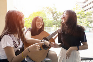 group of asian teenager happiness emotion playing spanish guitar on location