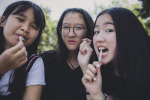 group of asian teenager relaxing and eating snack food