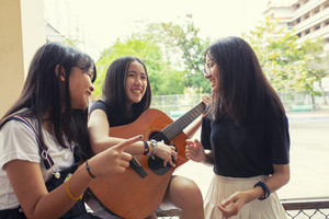 group of asian teenager standing outdoor plying spanish guitar and dancing with happiness emotion