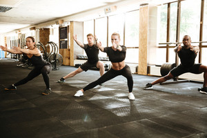 Group of diverse young people in sportswear doing stretching exercises together at the gym