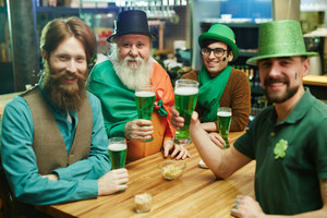Group of friendly men in traditional costumes toasting with glasses of beer in pub