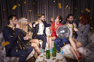 Group of friends celebrating new year among falling confetti