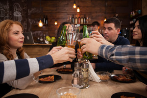 Group of happy friends drinking and toasting beer at brewery bar restaurant. Friendship celebration.